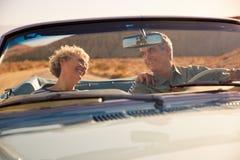Pares mayores en un viaje por carretera de los E.E.U.U., a través visto parabrisas del coche foto de archivo libre de regalías