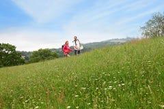Pares mayores en un viaje que camina en prado Foto de archivo libre de regalías