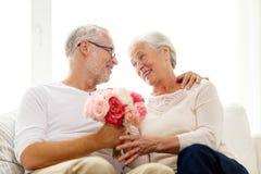 Pares mayores felices con el manojo de flores en casa fotos de archivo