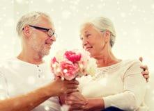 Pares mayores felices con el manojo de flores en casa Fotografía de archivo libre de regalías