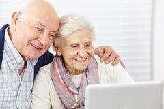 Pares mayores felices con el ordenador Fotografía de archivo