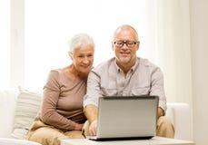 Pares mayores felices con el ordenador portátil en casa Fotografía de archivo libre de regalías