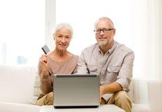 Pares mayores felices con el ordenador portátil y la tarjeta de crédito Imagen de archivo libre de regalías