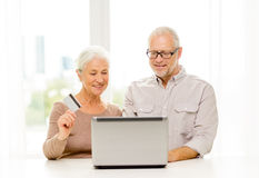 Pares mayores felices con el ordenador portátil y la tarjeta de crédito Imágenes de archivo libres de regalías