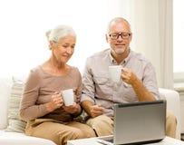 Pares mayores felices con el ordenador portátil y las tazas en casa Fotografía de archivo libre de regalías