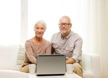 Pares mayores felices con el ordenador portátil y las tazas en casa Fotografía de archivo