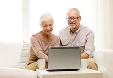 Pares mayores felices con el ordenador portátil y las tazas en casa Foto de archivo