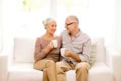 Pares mayores felices con las tazas en casa Fotos de archivo libres de regalías