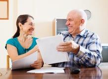 Pares mayores felices con los documentos foto de archivo libre de regalías