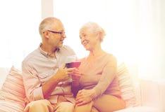 Pares mayores felices con los vidrios de vino rojo Fotografía de archivo libre de regalías