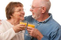 Pares mayores felices con los vidrios de zumo de naranja Fotos de archivo libres de regalías