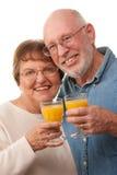 Pares mayores felices con los vidrios de zumo de naranja Imágenes de archivo libres de regalías