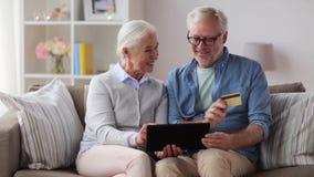 Pares mayores felices con PC de la tableta y la tarjeta de crédito almacen de metraje de vídeo