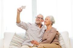 Pares mayores felices con smartphone en casa Imagen de archivo libre de regalías