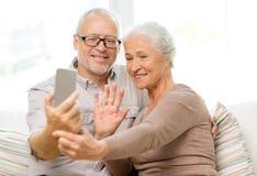 Pares mayores felices con smartphone en casa Foto de archivo