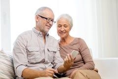 Pares mayores felices con smartphone en casa Imagen de archivo