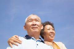 Pares mayores felices de los mayores con el fondo de la nube Foto de archivo libre de regalías