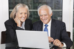 Pares mayores felices del negocio que miran la sentada blanca del ordenador portátil la tabla Fotos de archivo libres de regalías