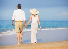 Pares mayores felices en la playa. Retiro Res tropical de lujo
