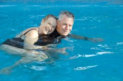 Pares mayores felices en piscina Imagen de archivo
