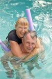 Pares mayores felices en piscina Imagenes de archivo