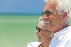 Pares mayores felices por el mar en una playa tropical Imagen de archivo libre de regalías