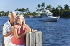 Pares mayores felices por River o el mar con el barco Imagen de archivo libre de regalías