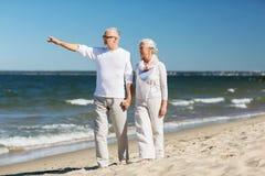 Pares mayores felices que caminan en la playa del verano Imagen de archivo libre de regalías