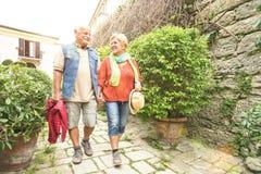 Pares mayores felices que caminan llevando a cabo la mano en la ciudad vieja de San Marino Imagen de archivo