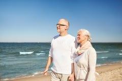 Pares mayores felices que caminan a lo largo de la playa del verano Foto de archivo libre de regalías