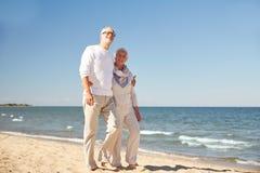 Pares mayores felices que caminan a lo largo de la playa del verano Imágenes de archivo libres de regalías