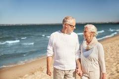 Pares mayores felices que caminan a lo largo de la playa del verano Fotos de archivo libres de regalías