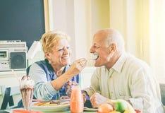 Pares mayores felices que comen las crepes en el desayuno en un restaurante de la barra - personas mayores que se divierten que d imagen de archivo