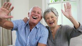 Pares mayores felices que dicen adiós con sus manos almacen de video