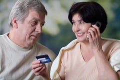 Pares mayores felices que hacen la verificación o hacer compras de la tarjeta Foto de archivo