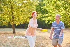 Pares mayores felices que juegan el disco volador Foto de archivo libre de regalías