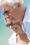 Pares mayores felices que miran al mar en una playa Imágenes de archivo libres de regalías