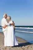 Pares mayores felices que miran al mar en una playa Foto de archivo libre de regalías