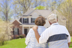 Pares mayores felices que miran el frente de la casa Imagen de archivo libre de regalías