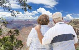 Pares mayores felices que miran hacia fuera sobre Grand Canyon Imagen de archivo
