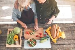 Pares mayores felices que preparan el almuerzo en cocina junto fotografía de archivo
