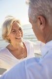 Pares mayores felices que recorren sosteniendo la playa tropical de las manos Imagen de archivo