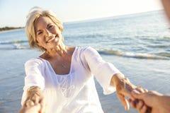 Pares mayores felices que recorren sosteniendo la playa tropical de las manos Fotografía de archivo