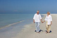 Pares mayores felices que recorren sosteniendo la playa tropical de las manos Fotos de archivo libres de regalías