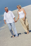 Pares mayores felices que recorren sosteniendo la playa tropical de las manos Imagen de archivo libre de regalías