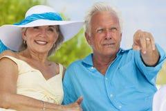 Pares mayores felices que señalan en una playa tropical Fotos de archivo