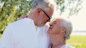 Pares mayores felices que se besan en el parque del verano almacen de video