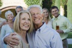 Pares mayores felices que se colocan así como el brazo alrededor Foto de archivo