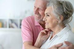 Pares mayores felices que se colocan de abarcamiento Foto de archivo libre de regalías