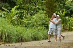 Pares mayores felices que se colocan de abarcamiento en un bosque tropical Foto de archivo libre de regalías